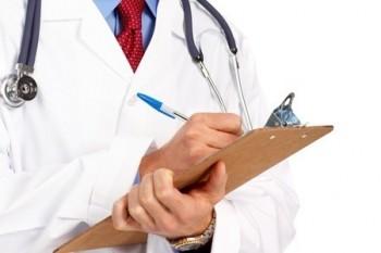 medico che scrive sulla cartella clinica con camice bianco e fonendoscopio appoggiato sul lato destro