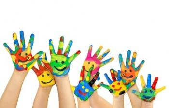 mani di bambini colorate e con disegni di visi sorridenti