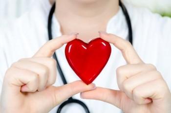 cuore rosso tra mani di una donna che indossa camice bianco e stetoscopio appoggiato al collo